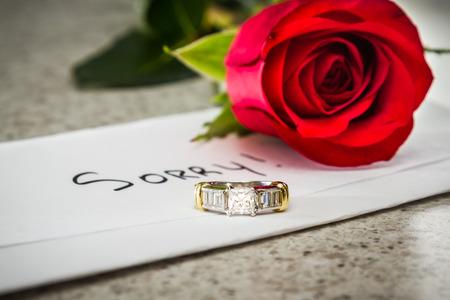 Het concept van een verloren relatie met een brief, een rode roos en een verlovingsring links op een tafel Stockfoto