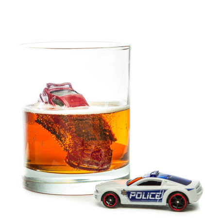 Image of a drunk driving accident inside a small glass with beer isolated on a white background