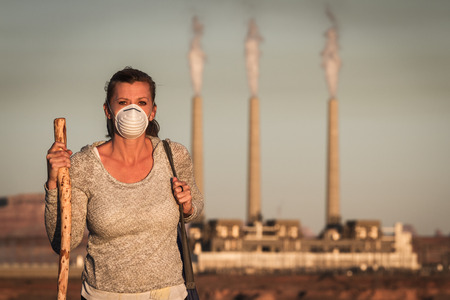 concept image of a woman wearing a mask and a walking stick walking away from a coal burning power plant with dirty smoke in the air Stock Photo