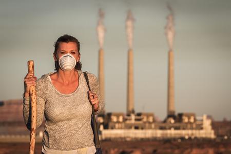 Concepto de imagen de una mujer que lleva una máscara y un bastón para caminar lejos de una planta de energía la quema de carbón con humo sucio en el aire Foto de archivo - 34113974
