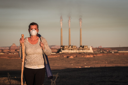 o2: concept image of a woman wearing a mask and a walking stick walking away from a coal burning power plant with dirty smoke in the air Stock Photo
