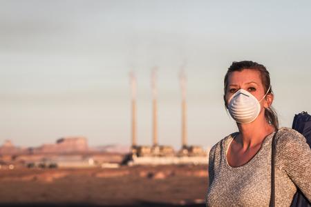concept beeld van een vrouw met een masker en een wandelstok lopen weg van een verbranding van kolen energiecentrale met vuile rook in de lucht Stockfoto