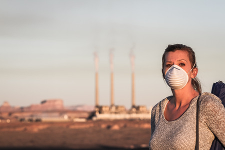 environmental issues: concept image of a woman wearing a mask and a walking stick walking away from a coal burning power plant with dirty smoke in the air Stock Photo