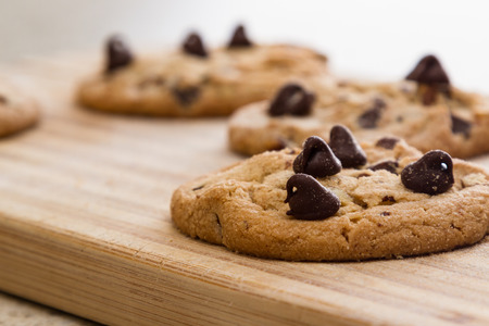 close up of a home made chocolate chip cookie on a wooden cutting board Zdjęcie Seryjne