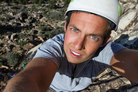 self portrait of a happy young man rock climbing in southern Utah photo