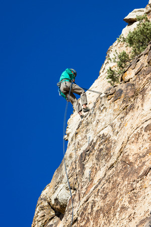 repelling: young man repelling down a sandstone cliff in youth western Utah