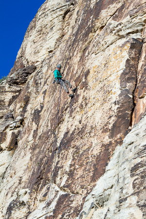 young man repelling down a sandstone cliff in youth western Utah photo