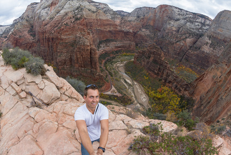 steep cliffs: young caucasian man taking a selfie over the steep cliffs of the  Angels Landing hiking trail in Zion NP
