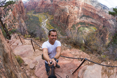 young caucasian man taking a selfie over the steep cliffs of the  Angels Landing hiking trail in Zion NP