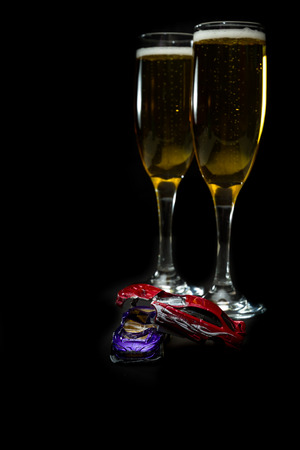 dwi: small crashed toy cars in front of champagne flutes as a be careful concept this holiday season