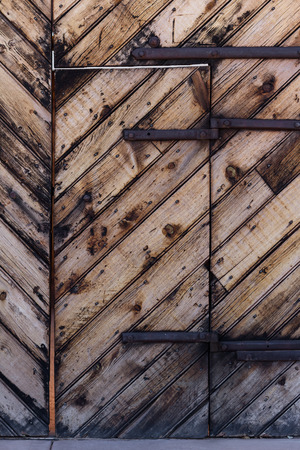 hinges: beautiful hand made wooden door with a v shaped pattern and rusted metal hinges