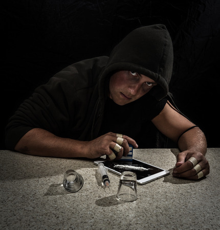young man pretending to be a drug addict for a concept image using a syringe, shot glasses and white powder