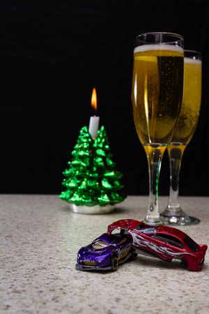 drink responsibly: small crashed toy cars in front of champagne flutes as a be careful concept this holiday season