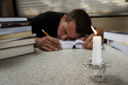 over worked: over worked researcher sleeping on an open book with many more on the table