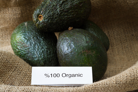 genetically modified organisms: food labeling concept with local organic avocados and an organic label
