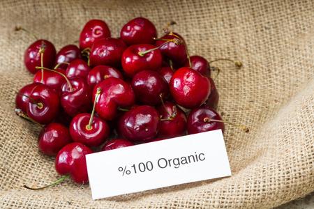 Lebensmittelkennzeichnung Konzept mit leuchtend roten Kirschen und einem Bio-Label Standard-Bild - 34689824