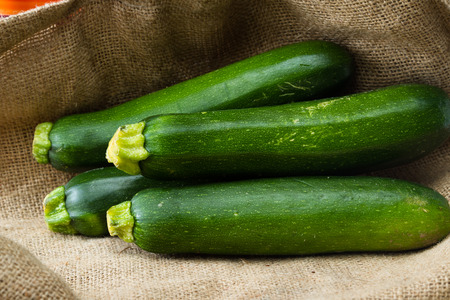 burlap sac: close up of fresh zucchini or green squash with a burlap sac as a background