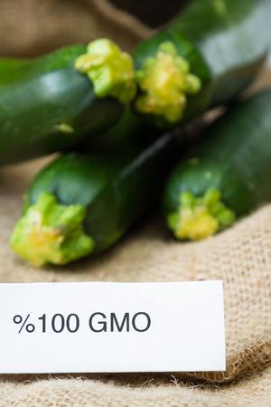 burlap sac: close up of fresh GMO zucchini or green squash with a burlap sac as a background