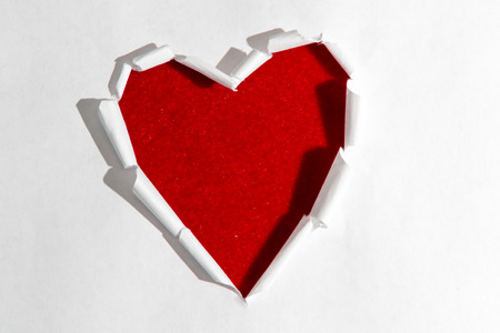 opening up: ripped white paper in the shape of a heart opening up to a red velvet texture