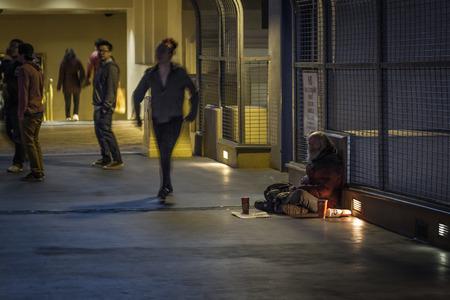 beggar's: Las Vegas Nevada - December 18 : Homeless man sitting on an overpass with tourist walking by, December 18 2014 in Las Vegas, Nevada Editorial
