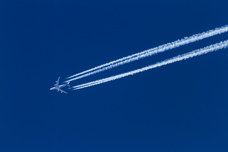 airplane leaving a long trail on a beautiful blue sky Editorial