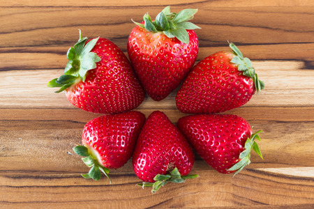 locally: locally grown organic strawberries arranged in a circle on a wooden table