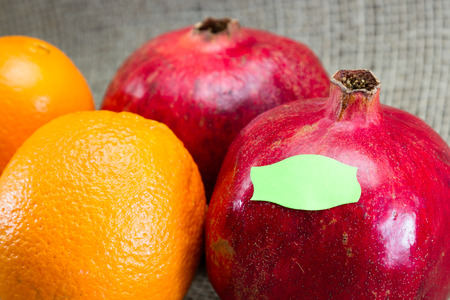 pesticide free: fresh pomegranates and oranges for a concept of labeling gmo vrs organic foods