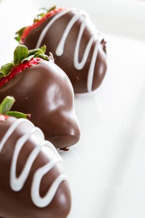 chocolate covered strawberries: mano bajaba fresas cubiertas de chocolate en un plato blanco Foto de archivo