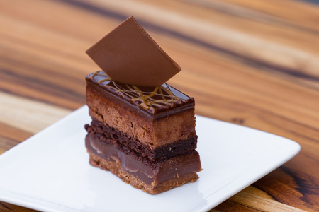 multiples: close up of a cake with multiples layers of chocolate and caramel garnished with a dark chocolate square