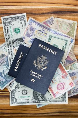 Americanos pasaportes en la parte superior de las monedas multinacionales sobre una mesa de madera Foto de archivo - 36334115