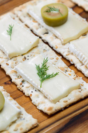 close up of slices of brie cheese on everything crackers with sliced of olives and fresh dill Stok Fotoğraf