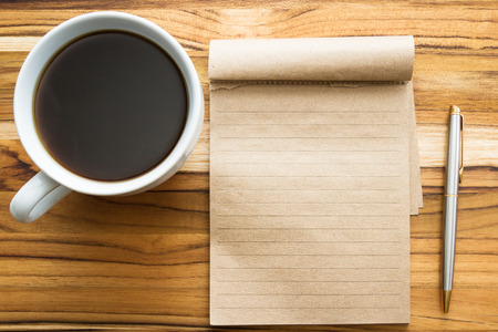 white work: fresh cup of coffee and a blank recycled note pad on a wooden background