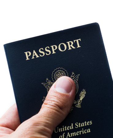 close up of a hand holding an american passport over a white background photo