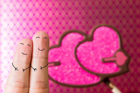 inseparable: love concept with two fingers with faces over a pink patter background