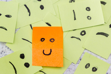 concept for a positive attitude with small office notes with multiple faces and one that stands out with a smile photo