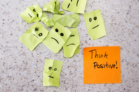 concept for a positive attitude with small crumbled up sad faces and a note with the phrase think positive photo
