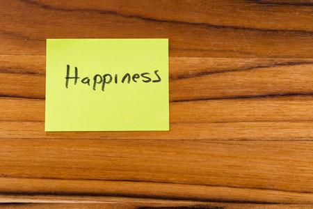 notitie op een houten bureau met het woord geluk geschreven op het