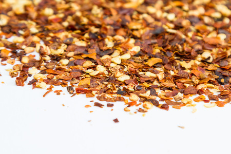 pepper flakes: close up of red pepper flakes on a white background Stock Photo
