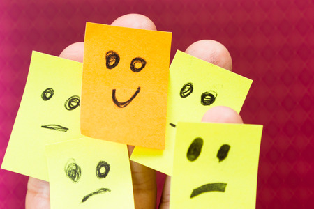 concept for optimism with paper faces on multiple fingers one with a happy good attitude Stock Photo