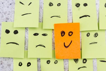 actitud positiva: concepto para una actitud positiva con peque�a oficina observa con m�ltiples caras y que se destaca con una sonrisa Foto de archivo