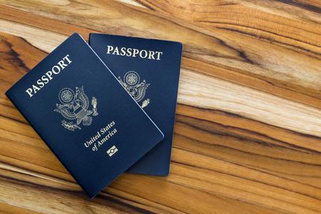 Cerca de dos pasaportes americanos en una mesa de madera para un concepto de viaje Foto de archivo - 36502540
