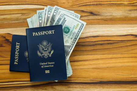 twenty two: close up of two american passports and cash money on a wooden table for a travel concept