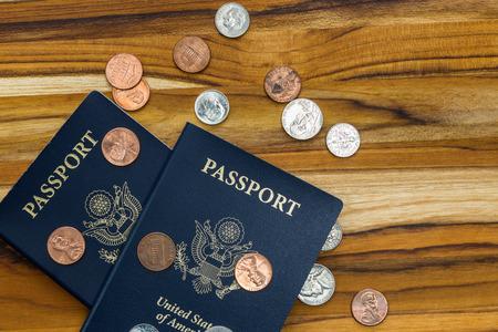 Cerca de dos pasaportes y las monedas de América para un concepto de viaje barato Foto de archivo - 36502547
