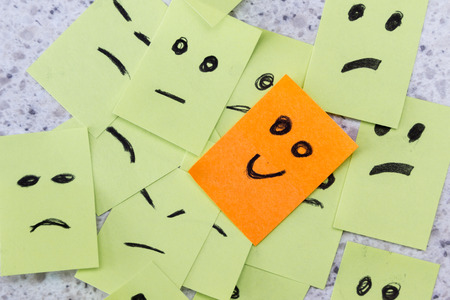 better days: concept for a positive attitude with small office notes with multiple faces and one that stands out with a smile