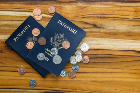 close up of two american passports and coins for a cheap travel concept