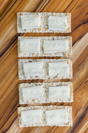 close up of slices of brie cheese on everything crackers on a wooden background