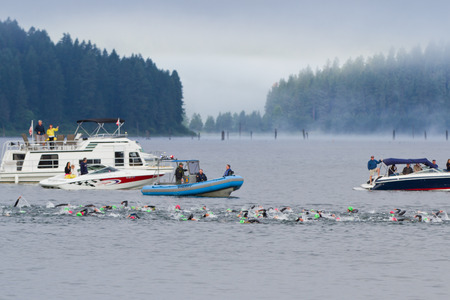 exert: COEUR D ALENE, ID - JUNE 23: Competitors for the ironman triathlon swimming early morning of June 23 2013 in Coeur d Alene Idaho Editorial