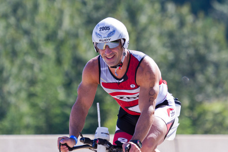 exert: COEUR D ALENE, ID -  JUNE 23: Dean Pappas, Triathlete on the bike part of the ironman triathlon, June 23 2013 in Coeur d Alene Idaho