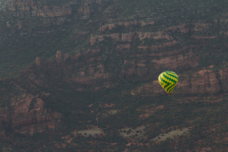 thru: Aerial view of Sedona Arizona with a Hot air balloon soaring thru the red rock landscape