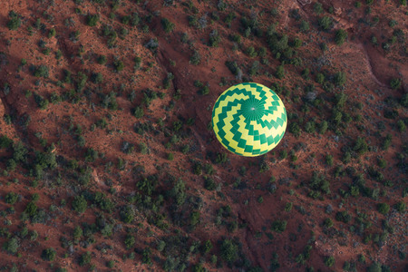 sedona: Aerial view of Sedona Arizona with a Hot air balloon soaring thru the red rock landscape
